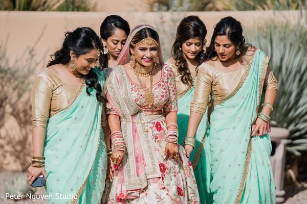 Sweet Indian bride posing with her bridesmaids outdoor capture.