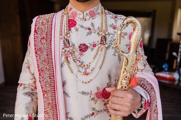 Closeup of Indian groom's sword, rani haar, dupatta and sherwani.