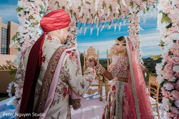 Glamorous Indian bride and groom walking in to mandap.