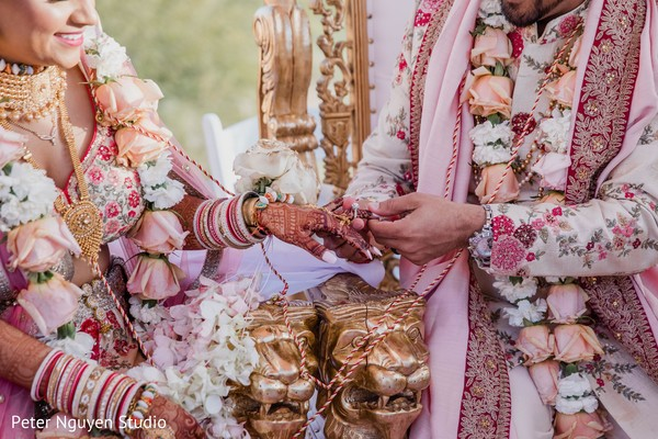 Indian groom putting the wedding band to bride.