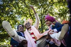 Indian groom being lifted by groomsmen