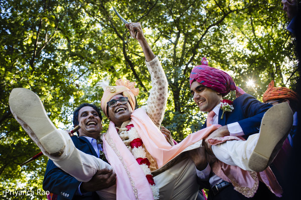 Indian groom being lifted by groomsmen