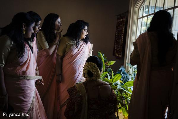 Indian bridesmaids and Maharani looking through the window
