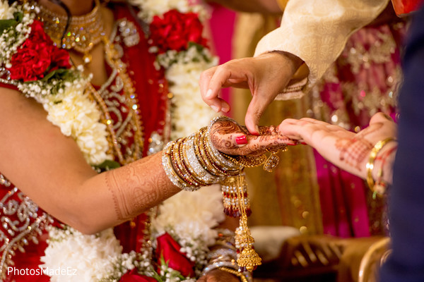 Indian bride getting a red mark on her hand.