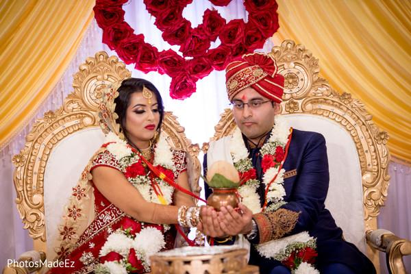 Maharani and groom holding the coconut ritual.