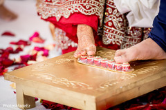 Indian bride and groom rolling betel nut with toes.