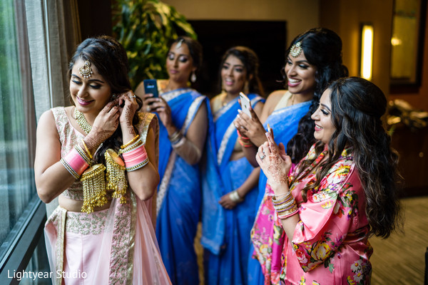 Indian bridesmaids taking pictures of Maharani.
