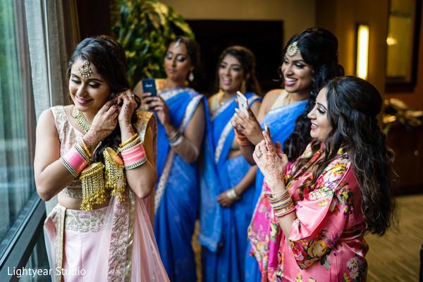 Indian bridesmaids taking pictures of Maharani.