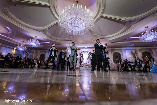 Indian groomsmen dancing at reception.