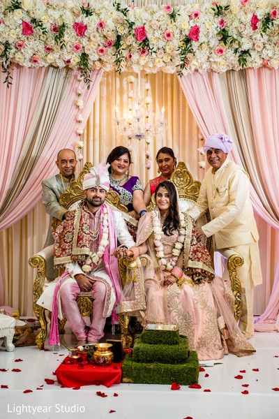 Indian lovebirds posing with parents at the mandap.