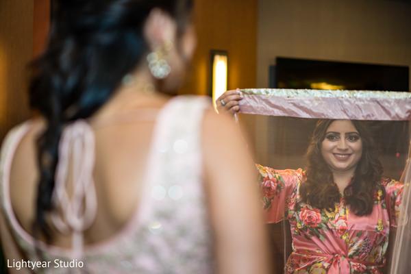 Indian bridesmaid putting ghoonghat to bride.