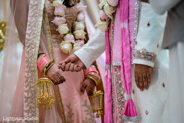 Closeup capture of Indian bride and groom holding at ceremony.