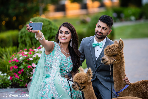 Indian couple taking a selfie with llamas.