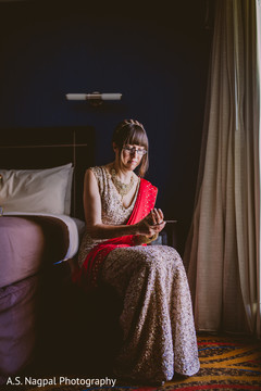 Lovely Indian bride putting her jewelry on.