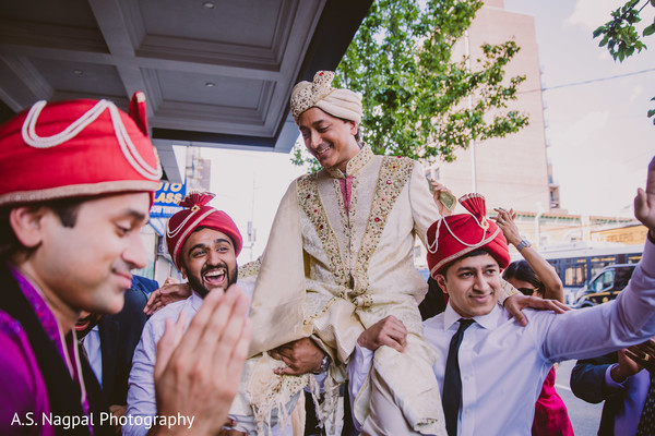 Elegant Indian groom lifted by groomsmen capture.