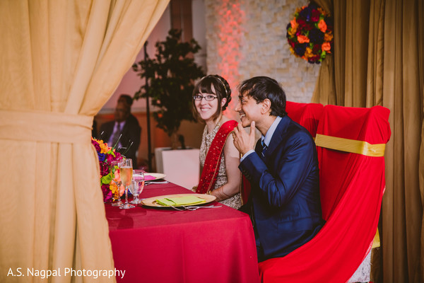 Indian couple at their wedding reception table.