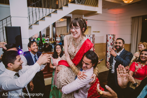 Maharani being lifted by groomsmen at reception party.