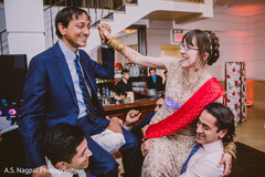 Indian bride and groom being lift up by groomsmen.