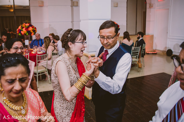 Indian bride dancing with relative.