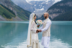 Indian bride and groom meeting by the lake