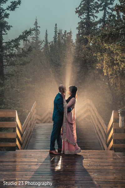 Amazing shot of Indian bride and groom by the trees