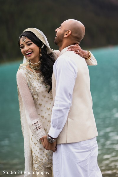 Indian bride and groom posing outdoors by the lake