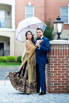 Glamorous Indian bride and groom posing for photoshoot.
