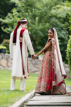 Indian bride holding hands with Raja during pictures