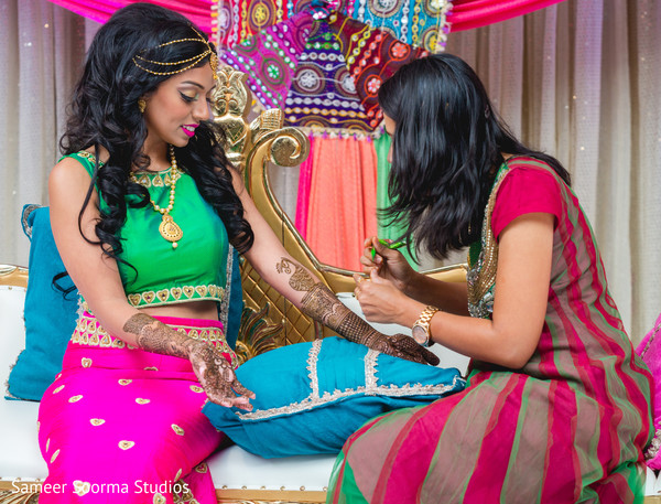 Dazzling Indian bride being assisted by mehndi artist