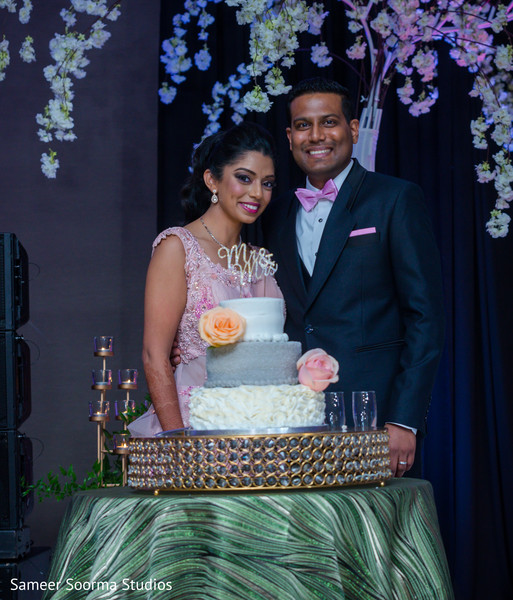 Indian bride and groom posing with cake
