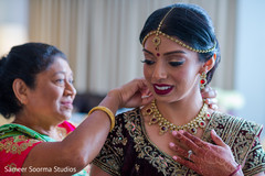 Indian bride being assisted by special guests prior to the ceremony