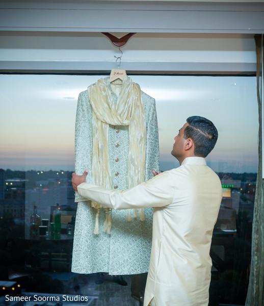 Indian groom admiring his elegant sherwani