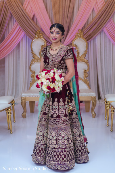 Dazzling Indian bride posing with bouquet