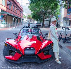 Indian groom posing by his ride