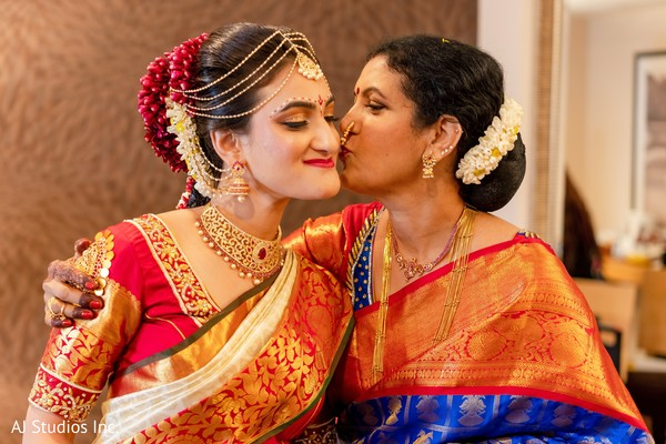 Lovely Indian bride being kiss by her mother.