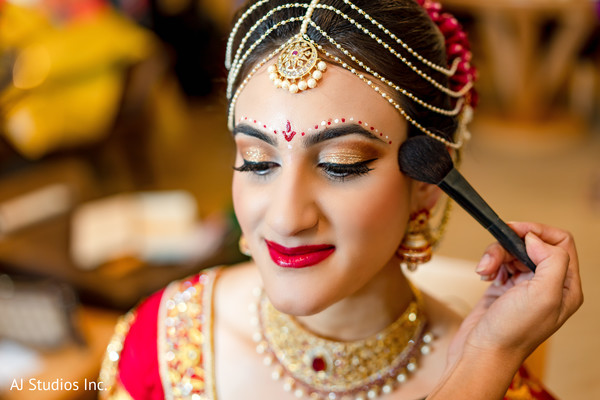 Indian bride getting the last touch ups of her makeup.