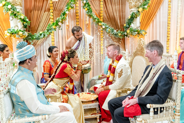 Maharani  throwing rice to Rajah at ceremony.