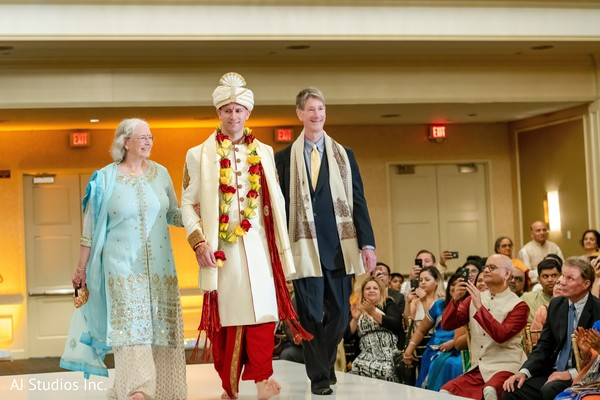 Indian groom making his entrance to the ceremony with parents.