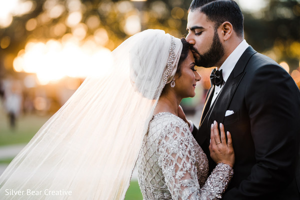Indian groom kissing the bride.