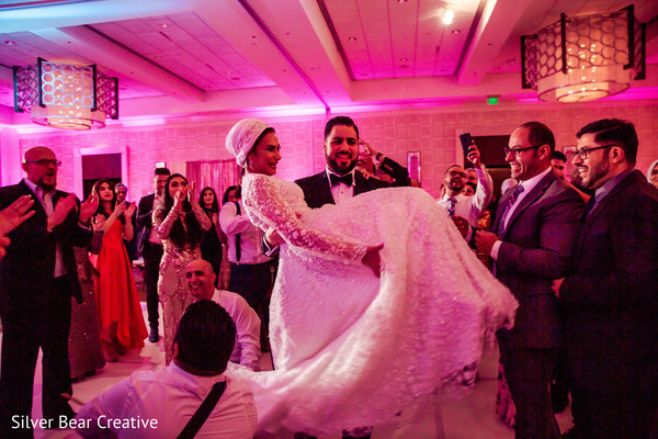 Indian bride and groom dancing with guests