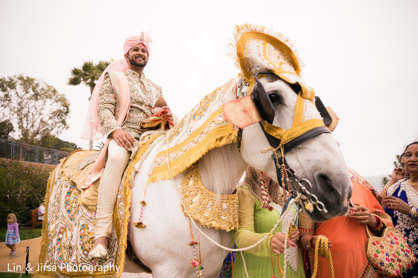 Charming Indian groom on his whit baraat horse.