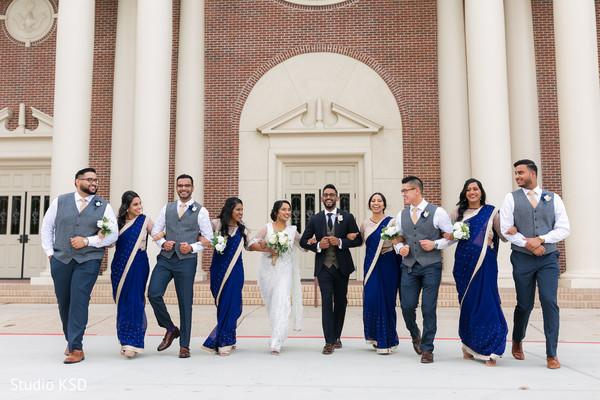 Fun photo shoot of bridesmaids and groomsmen with newlyweds
