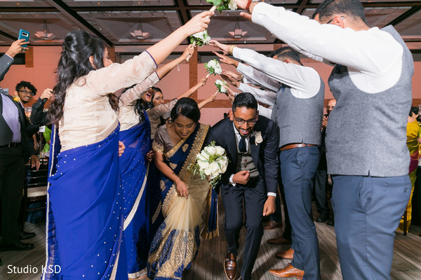 Indian newlyweds going through the groomsmen and bridesmaids