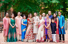 Indian bride and groom posing with family