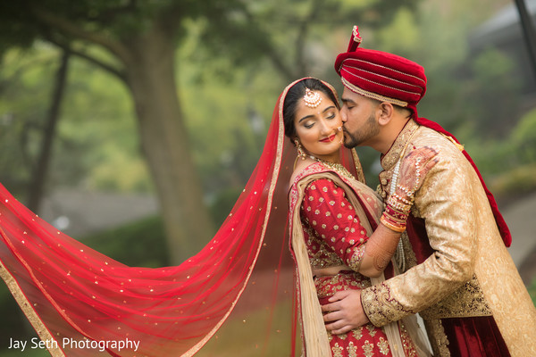 Indian groom hugging Indian bride on their wedding ceremony outfits.