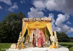 Ravishing Indian couple posing in mandap.