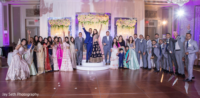 Indian couple with bridesmaids and groomsmen capture at the reception.