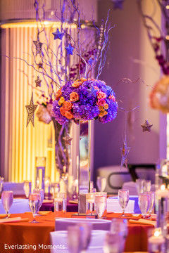 Orange and purple Indian wedding table centerpiece.