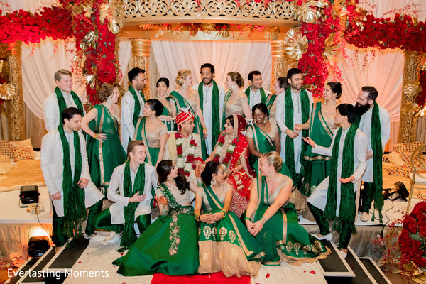 Indian bride and groom posing with bridesmaids and groomsmen.