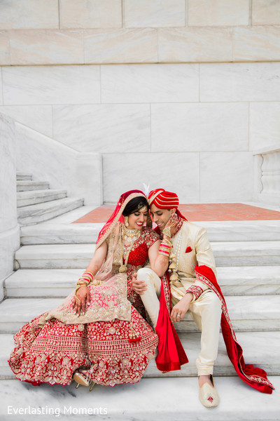 Lovely Indian  bride and groom seated on the stairs.